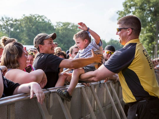 A security guard hands Gavin Bender, 4, back to his father after he joined Cassadee Pope on stage Friday at the Big Barrel Country Music Festival in Dover.