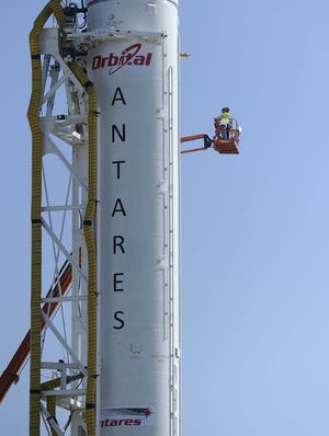 Workers in a crane look over Orbital Sciences' Antares rocket while on the launch pad at Wallops on April 16, 2013.