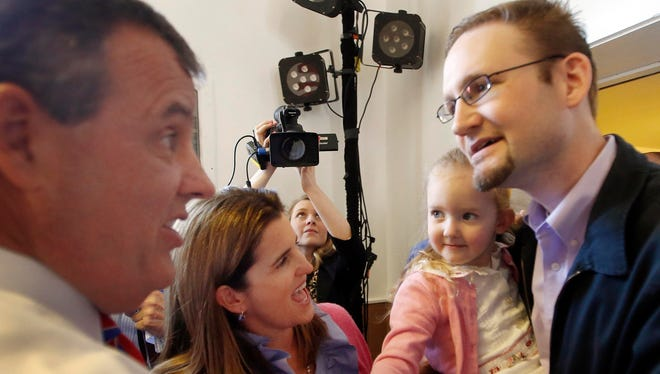 New Jersey Gov. Chris Christie, R-N.J., and his wife, Mary Pat, meet Nathon Wright and his 3-year-old daughter, Ellie, on April 15, 2015, during a town hall meeting in Londonderry, N.H.
