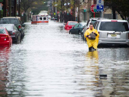 A resident walks through flood water and past a stalled