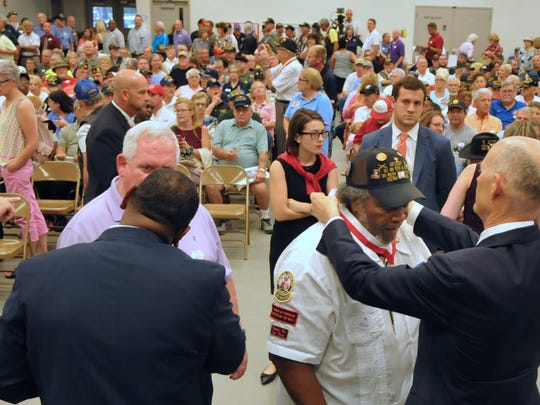Gov. Rick Scott places a medal around the neck of Marine veteran Theodis Ray of Titusville during a 2017 Governor's Veterans Service Award at Melbourne National Guard Armory. Hundreds of veterans from several wars, including World War II, Korea, Vietnam, Iraq and Afghanistan, were honored.