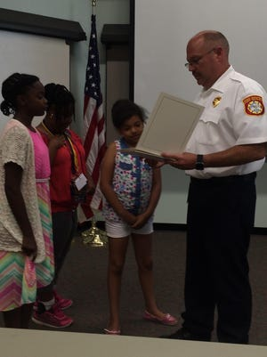 Fire Chief Jon Unruh reads from a civilian citation to Danielle McKay, Grace Thomas and Annisha Carter.