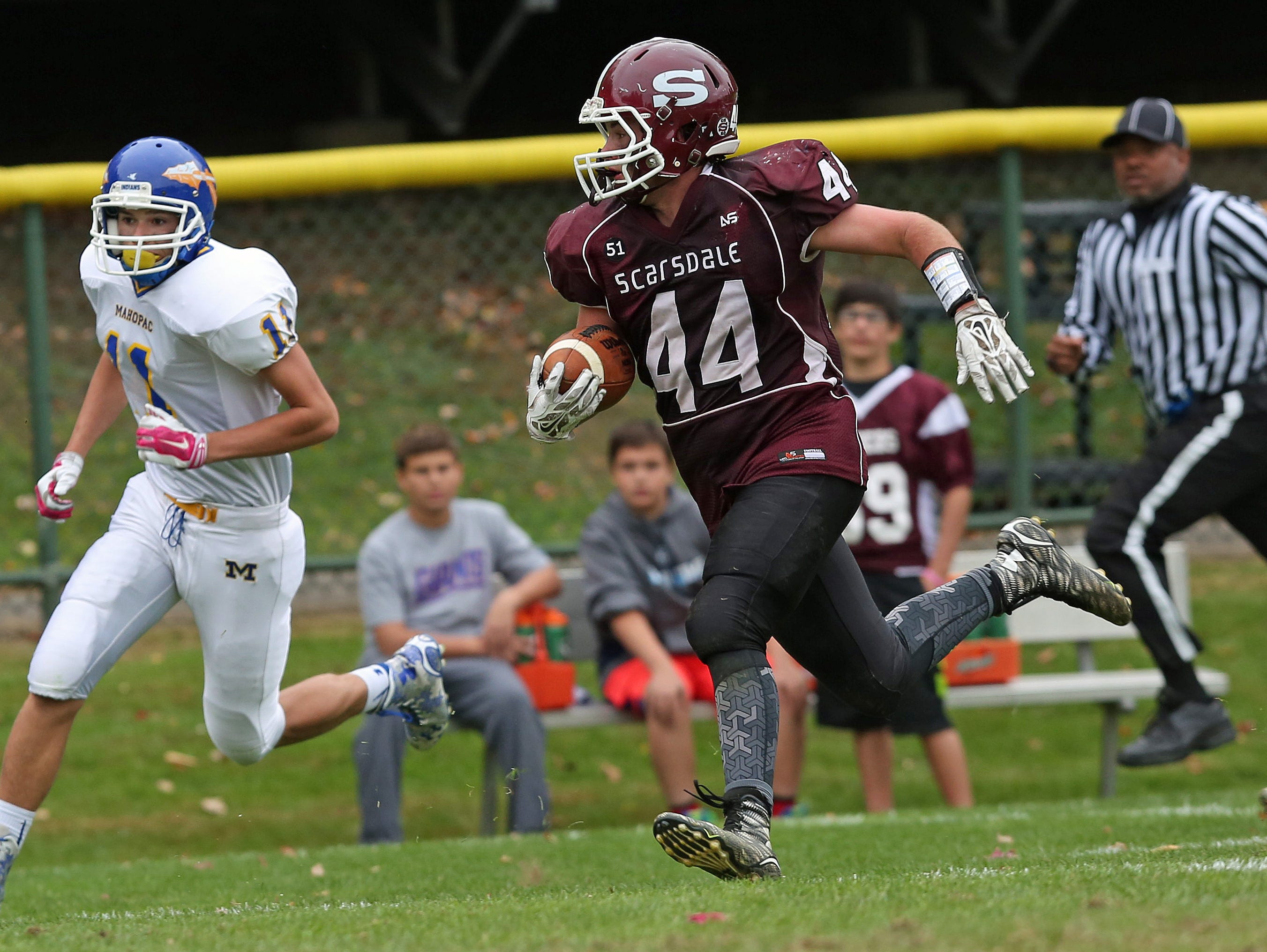Scarsdale's Stephen Nicholas (44) breaks away from Mahopac's Jonathan Jacklett (11)free on a first half touchdown run against Mahopac during football playoff game at Scarsdale High School Oct. 24, 2015. Scarsdale won the game 33-28.