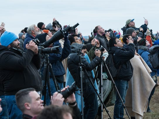 Spectators record a successful Antares rocket launch