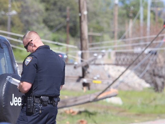 A Redding police officer investigates a crash that downed a power line near Eastside and Breslauer in south Redding Monday morning.