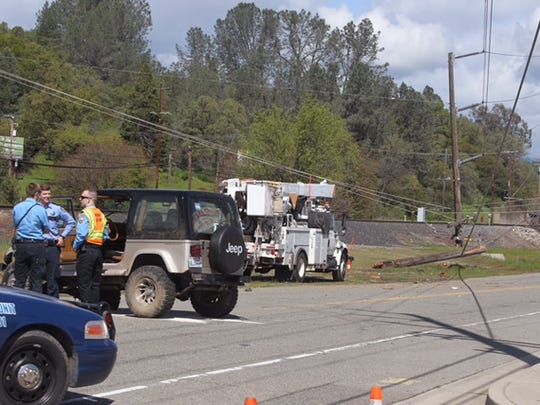 Law enforcement officers investigate a crash that downed a power line near Eastside Road and Breslauer in south Redding on Monday.