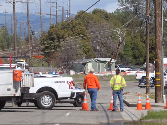 Crews work to remove a downed power line near Breslauer and Eastside Road in south Redding Monday.