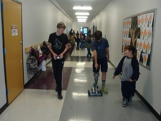 Students navigate a robotics project through the school