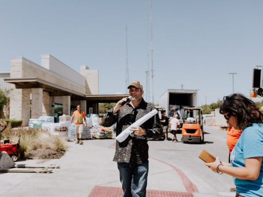Local restaurateur Joe Leone Introna talks to hurricane relief workers outside an Austin church earlier this month.