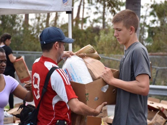 Barron Collier junior quarterback Sean Means, right, helps Harry Chapin Food Bank hand out food and supplies following Hurricane Irma at Parkside Elementary School on Sept. 15.
