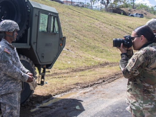Spc. Gabrielle Weaver, public affairs specialist with the 24th Press Camp Headquarters, takes a photo of a soldier with the Puerto Rico National Guard during the preparation for bridge reconstruction at Guajataca Dam, Puerto Rico.