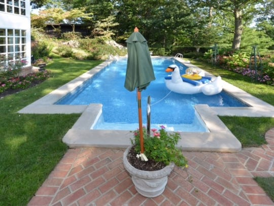 Your backyard oasis is perfect with an inground pool surrounded by lavish greenery.