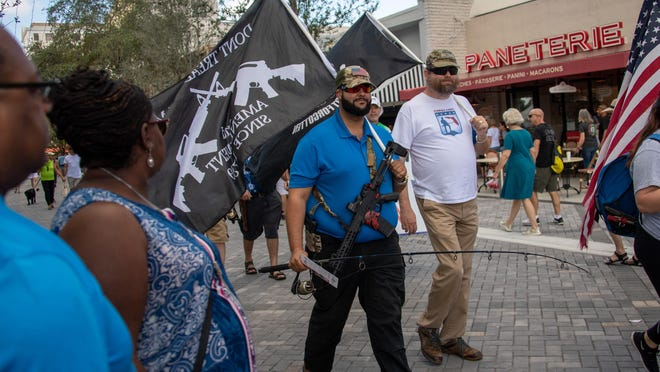 Gun rights activists march their way through Green Market shoppers on Saturday