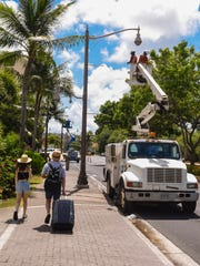 In this May 30 file photo, employees of Polyphase System Inc. work on replacing streetlight fixtures along San Vitores Road in Tumon.