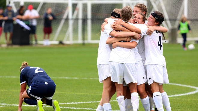 (L to R) Detroit Country Day #2 Jenna Staudt falls to the ground as Hudsonville Unity Christian celebrate at midfield after beating Detroit County Day during the second overtime in the girls soccer finals at Michigan State University in East Lansing, Michigan on Friday, June 12, 2015.