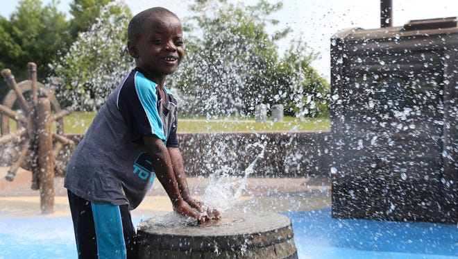 Jeremiah Raney,4, of Detroit has fun plugging the water hole on a barrel on Wednesday, July 29, 2015, at Mt. Elliott Park  & Pavilion in that features a Great Lakes schooner-themed water park in Detroit.
