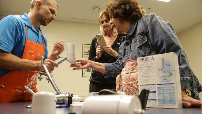 'I had my water tested a couple months ago but I'm not going to trust it,' Flint resident Sue Eremia (right) said after being taught how to properly use her free water filter by Home Depot master plumber Ryan Fotenakes that Flint residents received at the Genesee County Community Action Resource Department on Lippincott in Flint on Tuesday October 6, 2015.