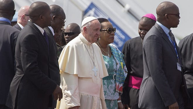Pope Francis walks beside Catherine Samba-Panza, president of the Central African Republic after landing in Bangui on Nov. 29, 2015.