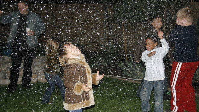 """Some of Marley Park's youngest residents delight in watching """"snow"""" fall during a past festival. The Marley Park community in Surprise has elements of a """"village"""" concept with recreation amenities and gathering places for residents."""