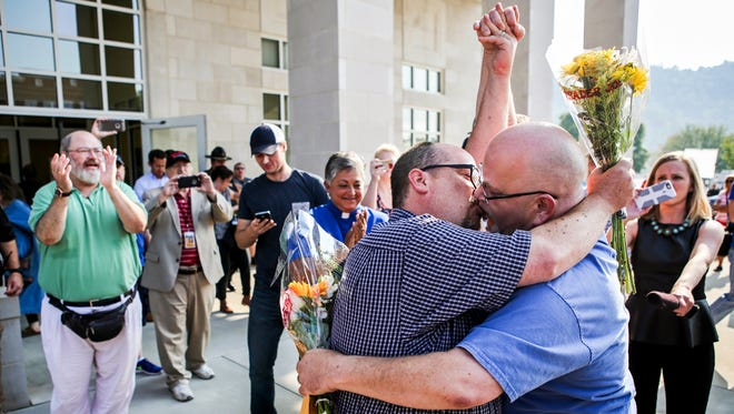 """Michael Long, left, and Timothy Long kiss outside the Rowan County Clerk's Office on Friday raising their fist clinched high in to the air after being the second couple to receive marriage license documents following the Kim Davis ruling on Thursday. """"In our minds, we've always been married,"""" Timothy said. Sept. 4, 2015The events surrounding Kim Davis' gay marriage stance in Rowan County may have been the most emotionally riveting assignment I've covered to date. It almost didn't feel like reality, the magnitude of the emotions displayed on the streets outside the court hearing. The next morning, watching the first couples to recieve their marriage licenses, the sounds of frustration and anger, hate and opinion, succumbed to the sounds of cheers and applause. I'll never forget that feeling."""