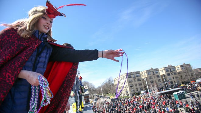 Grace Lowell, 11, of Grosse Pointe Park tosses beads to revelers from the roof of the Traffic Jam & Snug restaurant before the start of Detroit's annual Marche du Nain Rouge on Sunday, March 20, 2016.
