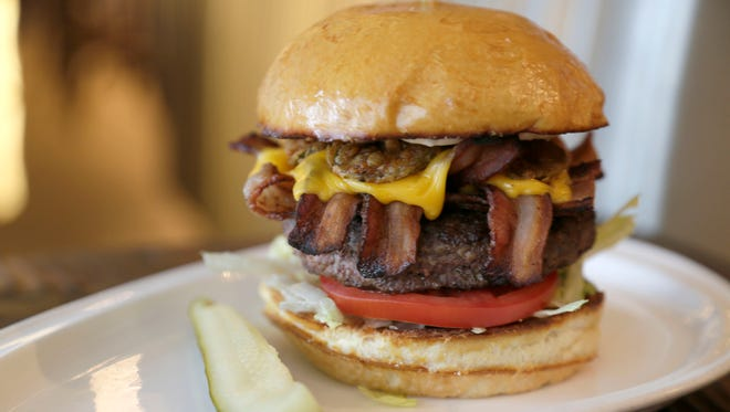 The Central burger with fried pickles, American cheese, lettuce, tomato, bacon and bistro sauce on brioche bun.  The Central Kitchen + Bar is in the First National Bank Building in downtown Detroit.