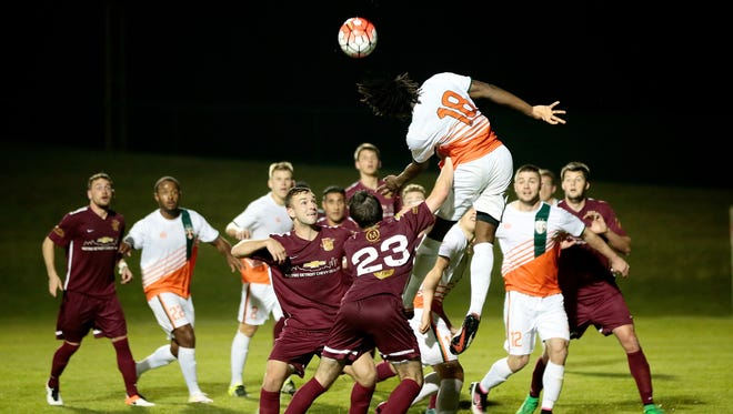 Michigan Bucks defender Lalas Abubakar heads the ball during DCFC's 1-0 win over the Michigan Bucks on penalty kicks in the first round of the U.S. Open Cup tournament Wednesday at Oakland University.