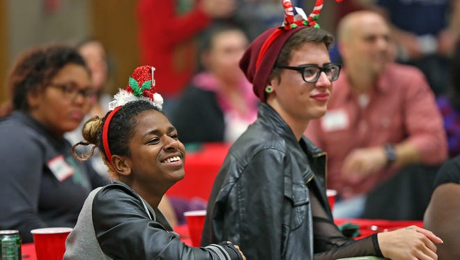 Meya Wright, left, and Brandon Boggs smile as they watch entertainment during the Outreach Indiana Christmas party, held at Englewood Church, Tuesday, December 13, 2016.  The nonprofit supports homeless teens and young adults.