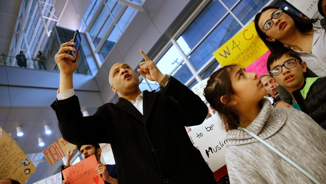 US Congressman Andre Carson, left, chants slogans with others during the protest at the Indianapolis Airport, Sunday, January 29, 2017, against President Donald Trump's executive orders on immigration.