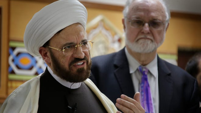 Members of the interfaith community lead by Imam Mohammad Ali Elahi, left, with Rev. Ed Rowe by his side assemble for a press conference Wednesday Feb. 1, 2017 at the Dearborn Heights Islamic House of Wisdom regarding President Trump's order on immigrants..