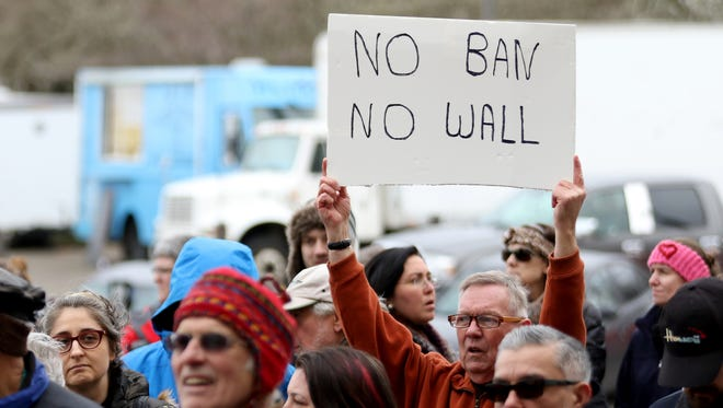 Randy Fraser, of Salem, carries a sign during an immigrant and refugee rights rally, in respone to President Trump's ban on people entering the United States from seven Muslim-majority countries, at the Oregon State Capitol in Salem on Wednesday, Feb. 1, 2017.