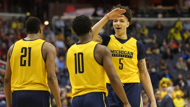Michigan Wolverines forward D.J. Wilson (5) celebrates with guard Derrick Walton Jr. (10) after a call against Illinois during the second half of U-M's 75-55 win in the Big Ten tournament March 9, 2017 at Verizon Center.