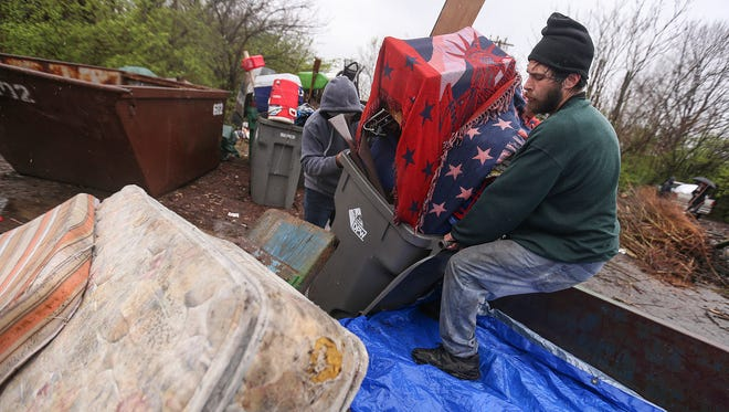 Former resident Zach Mendenhall loads his belongings into a truck trailer for relocation, at the Jungle homeless camp, Indianapolis, Friday, March 31, 2017. Campsites were mostly vacant by Friday morning, though about a dozen residents remained. At 9:15 a.m., the CSX Transportation Railroad Police began taking down tents that were not yet collapsed.