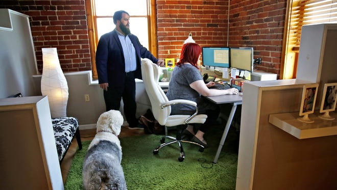Branch Manager Michael Partin talks with staff as office pet, Millie, tags along at Parker Mortgage Team, a group in the Finance of America Mortgage company.  The Noblesville branch is one of the Top Workplaces for 2017 in Central Indiana.