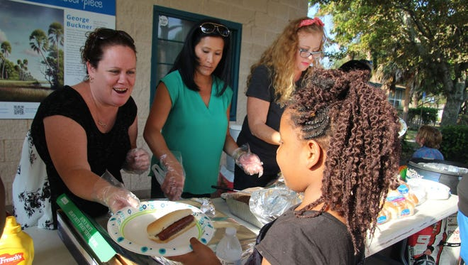 Jessica Brooks passes out hot dogs and hamburgers to members of the Gifford Community.