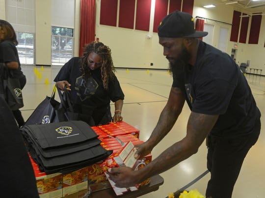 Pro basketball free agent Reggie Evans puts togehter food bags Saturday during the Reggie Evans Foundation Annual Turkey Giveaway at the Woodland Heights Resource Center. Reggie gave away 400 turkeys with stuffing and green beans.