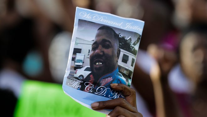 A woman holds a photo of Alton Sterling during a protest against the July 5 shooting of Sterling, an African-American shot dead while being taken into custody by two white police officers, in Baton Rouge July 9, 2016.