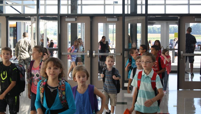 Students stream into the front lobby of Oakland Elementary School in August 2015 on their first day of classes in the district's newest school.