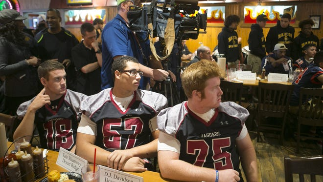 Desert Ridge High football players Tate Shumway, (from left) D.J. Davidson and Nick Hannon, look on during the AIA high school football championship media day at Famous Dave's Bar-B-Que in Mesa on Tuesday, November 24, 2015.