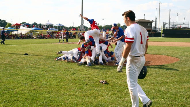 Roncalli Rebels baseball players pile on top of each other in celebration of their 8-5 semistate victory Saturday against Center Grove.