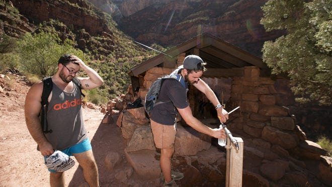 Liam Richardson of Canberra, Australia, fills a water bottle from the Grand Canyon Trans-Canyon Pipeline, as his friend, Cameron Smith, also of Canberra, Australia, wipes sweat on his head, as the pair hike along the Bright Angel Trail above Indian Garden in Grand Canyon National Park on July 14, 2016. The Trans Canyon-Canyon Pipeline which was built between 1965 and 1970 brings water 15 miles from Roaring Springs below the North Rim all the way to the South Rim. The pipeline which is nearing 50 years old is continuously breaking making replacement necessary.