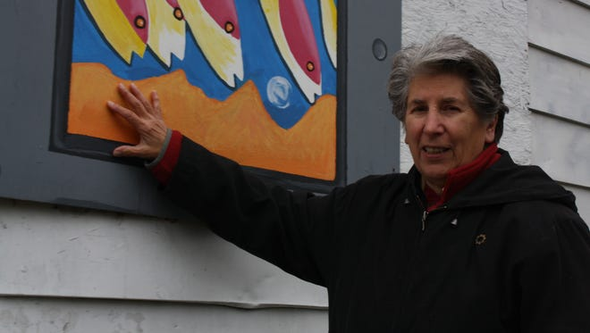 Peg Johnson stands next to her favorite mural that she helped create. on the corners of Jarvis and Charlotte ave.