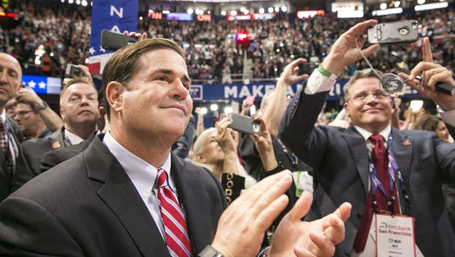 Gov. Doug Ducey cheers with Robert Graham, chairman of the Arizona Republican Party, at the QuickenLoans Arena in Cleveland after Donald Trump wins the Republican nomination for president during the Republican National Convention on July 19, 2016.