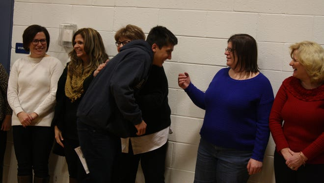 Nicholas Miller, 17, of Binghamton, hugs his fifth grade teachers during the 'Life After Coolidge' Celebration.