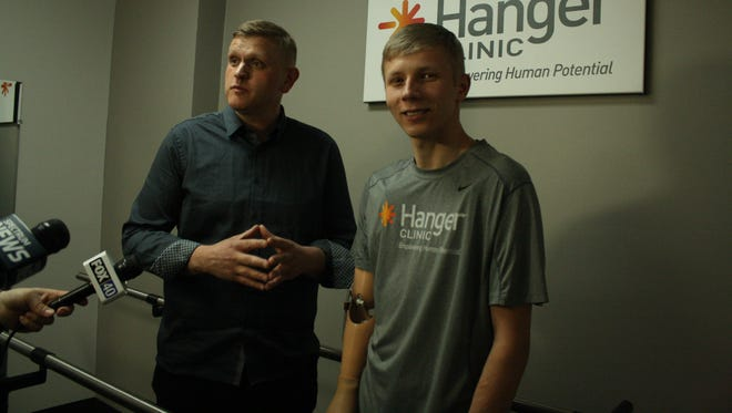 Anatoliy Pradun (left) and Sergiy Bilan (right) explain Bilan's process of receiving medical treatment in the United States after being wounded in Ukraine.