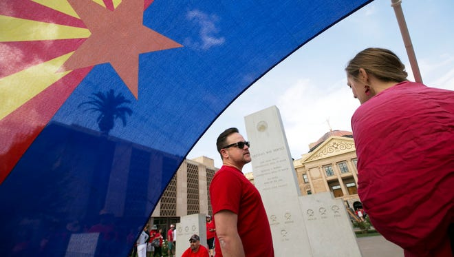 Eric Peterson, a history teacher at Scottsdale Unified School District, and Baily Hershberger, a teacher at Phoenix Union High School District, rally during the fifth day of the Arizona teacher walkout at the state Capitol in Phoenix on May 2, 2018.