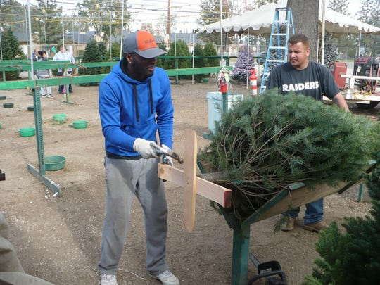 Kayron Stephens, left, hammers in a nail into a Christmas