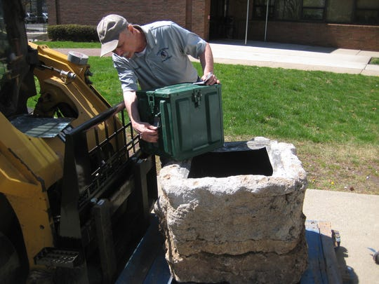A Clifton public works employee removes the time capsule from a cement enclosure which helped keep the contents in pristine condition, centennial organizers said.