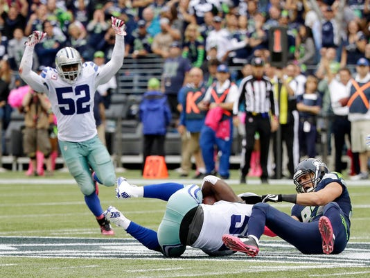 Dallas Cowboys middle linebacker Rolando McClain, center, comes down with an interception on a pass intended for Seattle Seahawks tight end Luke Willson, right, as Cowboys' Justin Durant (52) celebrates late in the second half of an NFL football game, Sunday, Oct. 12, 2014, in Seattle. The Cowboys beat the Seahawks 30-23. (AP Photo/Elaine Thompson)