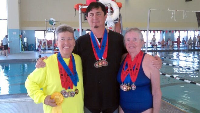 Senior Olympic swimmers, from left, Pamela Gulbrandson, Ben Young and Yenny van Dinter show off their medal haul at the New Mexico Games held July 13-16, in Roswell, NM.